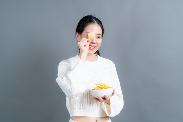 Young asian woman in white sweater eatting potato chips on grey background