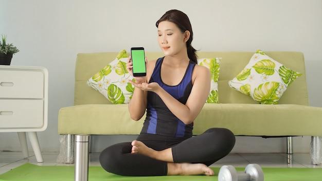 스마트폰 화면을 보여주는 요가를 마친 젊은 아시아 여성