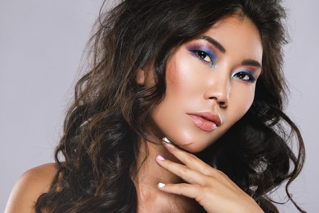 美しい巻き毛とメイクの若いアジア女性