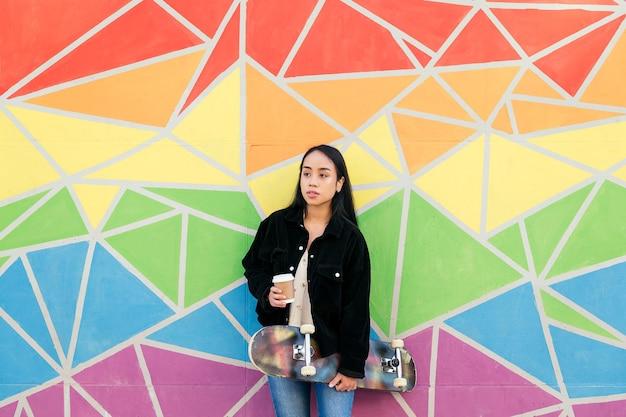 다채로운 벽에 기대어 손에 커피와 스케이트보드를 들고 있는 젊은 아시아 여성