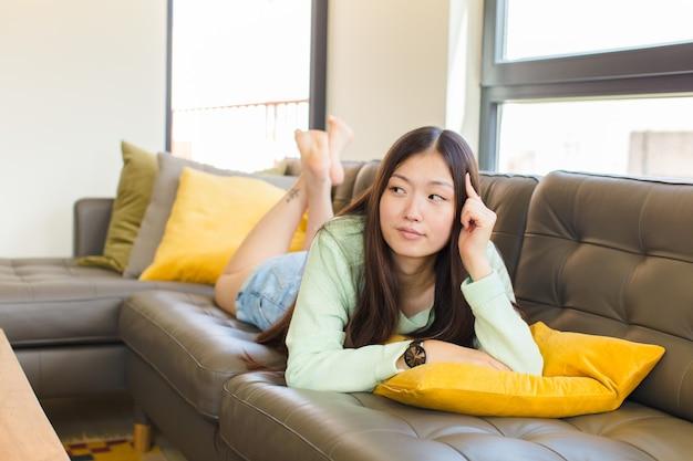 집중된 표정으로 젊은 아시아 여성, 의심스러운 표정으로 궁금해