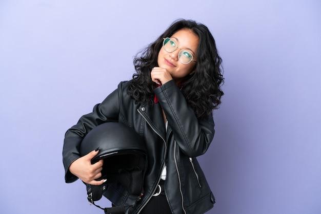 Молодая азиатская женщина с мотоциклетным шлемом изолирована на фиолетовом фоне и смотрит вверх