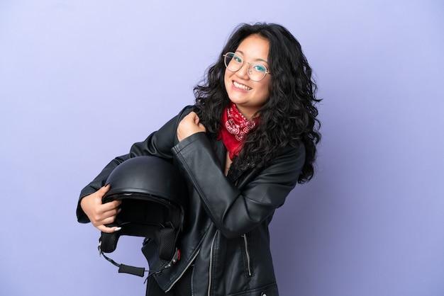 Молодая азиатская женщина с мотоциклетным шлемом изолирована на фиолетовом фоне празднует победу