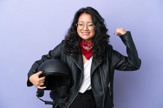 Молодая азиатская женщина с мотоциклетным шлемом изолирована на фиолетовом фоне, делая сильный жест