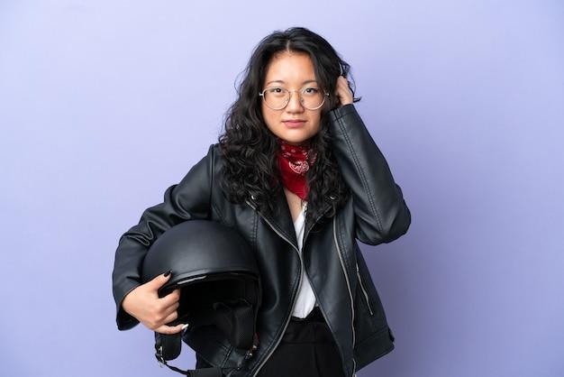 Молодая азиатская женщина с мотоциклетным шлемом изолирована на фиолетовом фоне разочарована и закрывает уши