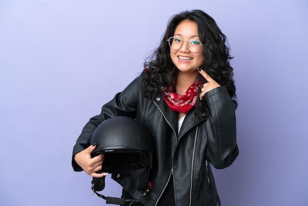 Молодая азиатская женщина с мотоциклетным шлемом изолирована на фиолетовом фоне, показывая жест пальца вверх