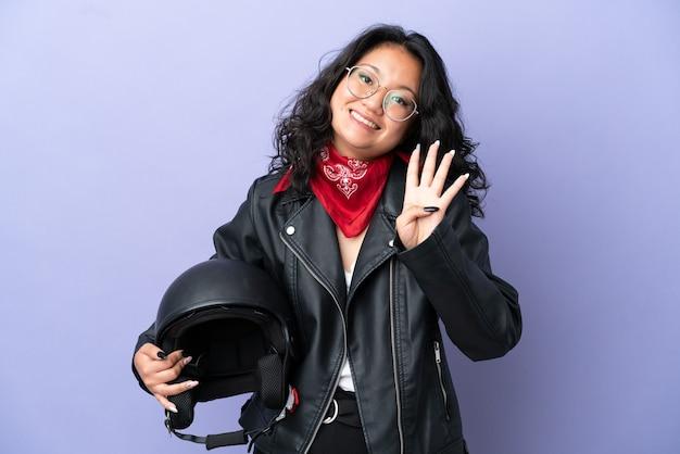 Молодая азиатская женщина с мотоциклетным шлемом изолирована на фиолетовом фоне счастлива и считает четыре пальцами