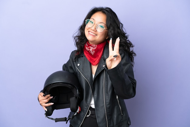 Молодая азиатская женщина с мотоциклетным шлемом изолирована на фиолетовом фоне счастлива и считает три пальцами