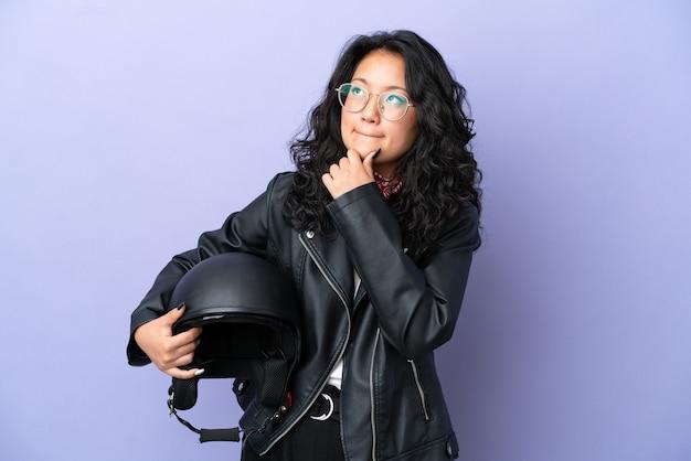 보라색 배경에 오토바이 헬멧을 쓴 젊은 아시아 여성이 의심과 생각을 갖고 있다