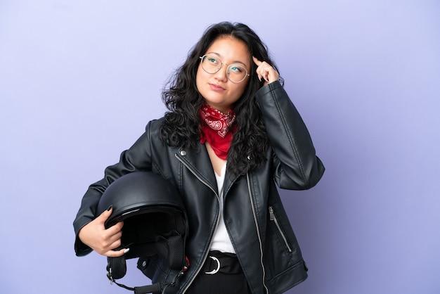疑いと思考を持っている紫色の背景に分離されたオートバイのヘルメットを持つ若いアジアの女性