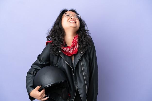 Молодая азиатская женщина с мотоциклетным шлемом изолирована на фиолетовом фоне смеясь