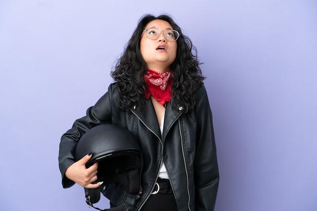 Молодая азиатская женщина с мотоциклетным шлемом изолирована на фиолетовом фоне, глядя вверх и с удивленным выражением лица