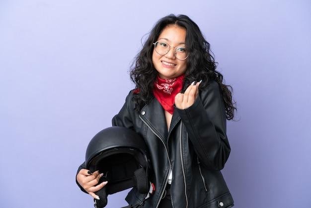 Молодая азиатская женщина с мотоциклетным шлемом изолирована на фиолетовом фоне, делая денежный жест
