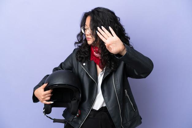 Молодая азиатская женщина с мотоциклетным шлемом изолирована на фиолетовом фоне, делая жест стоп и разочарованная