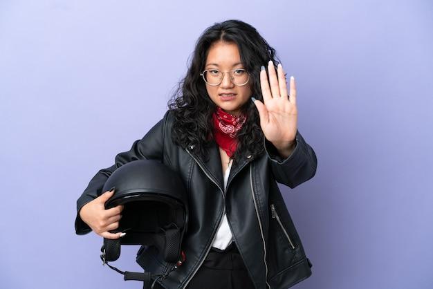Молодая азиатская женщина с мотоциклетным шлемом изолирована на фиолетовом фоне, делая стоп-жест