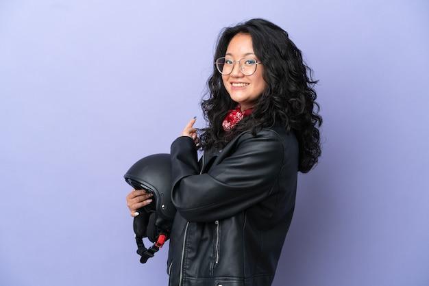 Молодая азиатская женщина с мотоциклетным шлемом изолирована на фиолетовом фоне, указывая назад