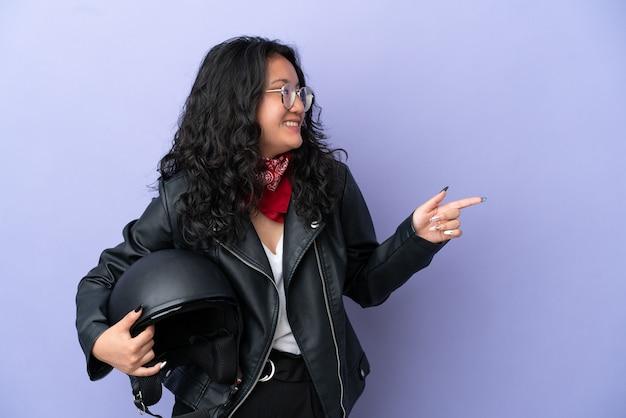 Молодая азиатская женщина с мотоциклетным шлемом изолирована на фиолетовом фоне, указывая пальцем в сторону и представляет продукт