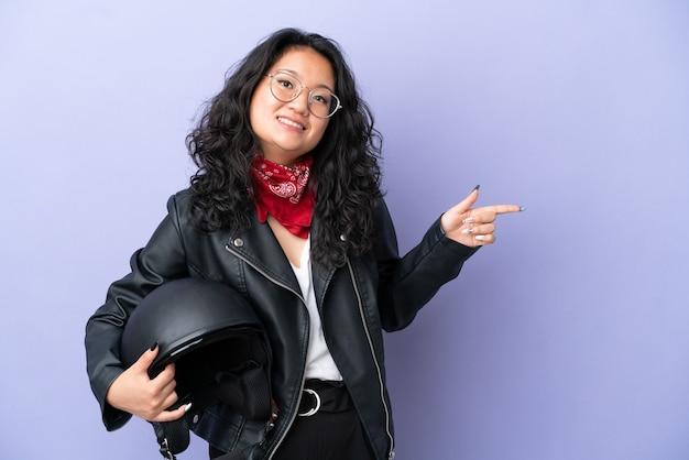 Молодая азиатская женщина с мотоциклетным шлемом изолирована на фиолетовом фоне, указывая пальцем в сторону