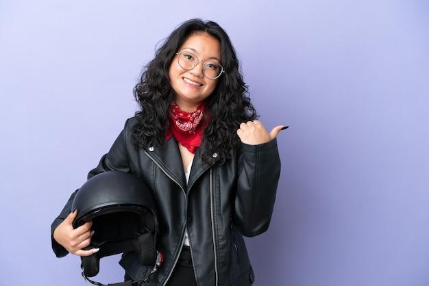 Молодая азиатская женщина с мотоциклетным шлемом изолирована на фиолетовом фоне, указывая в сторону, чтобы представить продукт
