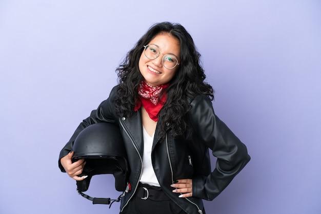 Молодая азиатская женщина с мотоциклетным шлемом изолирована на фиолетовом фоне, позирует с руками на бедре и улыбается