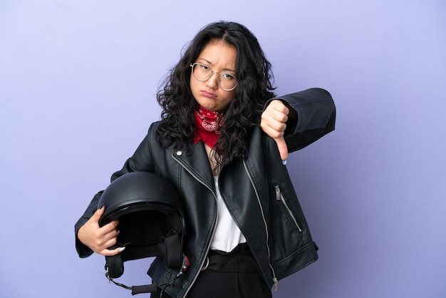Молодая азиатская женщина с мотоциклетным шлемом изолирована на фиолетовом фоне, показывая большой палец вниз с отрицательным выражением лица