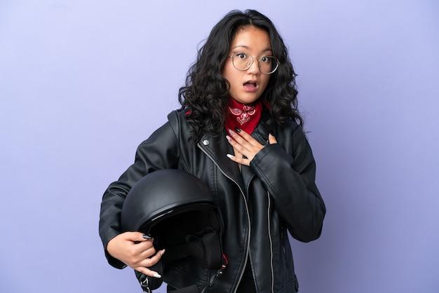 Молодая азиатская женщина с мотоциклетным шлемом на фиолетовом фоне удивлена и шокирована, глядя вправо