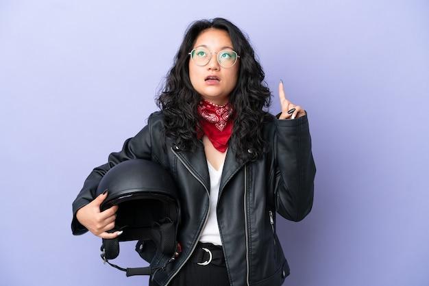 指を上に向けるアイデアを考えて紫色の背景に分離されたオートバイのヘルメットを持つ若いアジアの女性