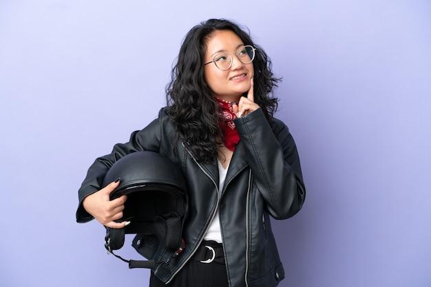 見上げながらアイデアを考えて紫色の背景に分離されたオートバイのヘルメットを持つ若いアジアの女性