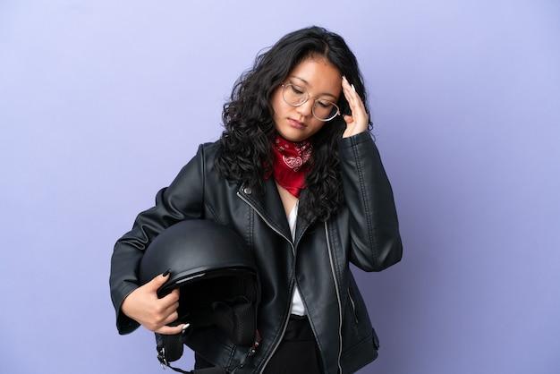 Молодая азиатская женщина с мотоциклетным шлемом изолирована на фиолетовом фоне с головной болью