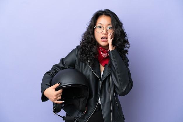 Молодая азиатская женщина в мотоциклетном шлеме изолирована на фиолетовом фоне с удивленным и шокированным выражением лица