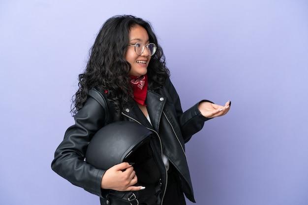 Молодая азиатская женщина с мотоциклетным шлемом изолирована на фиолетовом фоне с удивленным выражением лица, глядя в сторону