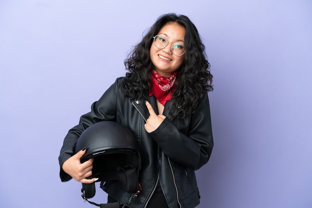驚きの表情で紫色の背景に分離されたオートバイのヘルメットを持つ若いアジアの女性
