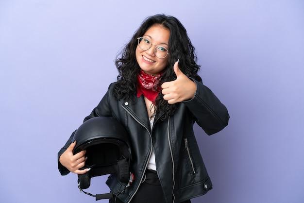 Молодая азиатская женщина с мотоциклетным шлемом изолирована на фиолетовом фоне с большими пальцами руки вверх, потому что произошло что-то хорошее