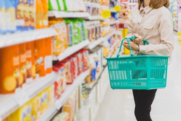 スーパーマーケットでバスケットを持つ若いアジア女性。ショッピング、消費者および人々の概念。