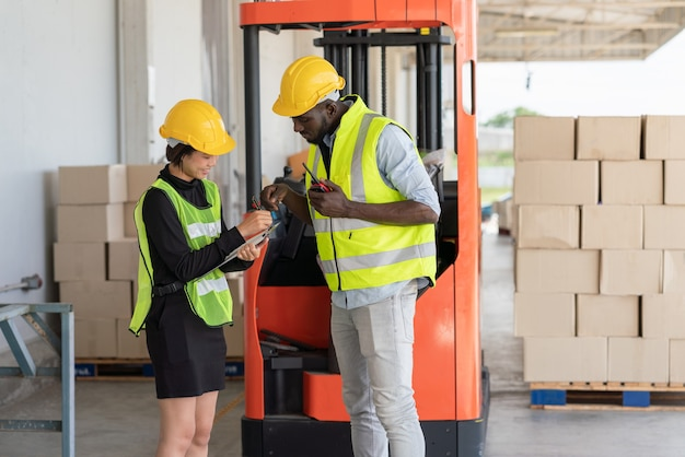 창고 공장에서 일하는 동안 안전 조끼와 노란색 헬멧을 쓴 흑인 노동자가 문서를 함께 보고 있는 젊은 아시아 여성