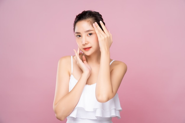 Young asian woman with clean fresh white skin touching her own face softly in beauty pose