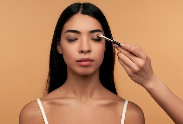 白いトップで清潔で健康的な輝く肌を持つ若いアジアの女性は、ベージュで分離されたブラシでアイシャドウを適用して、アイメイクをしています