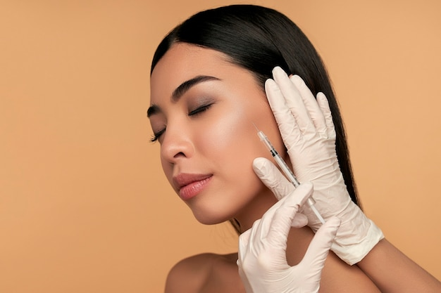 Young asian woman with clean radiant skin gets botox injections for contour tightening, lip augmentation on beige