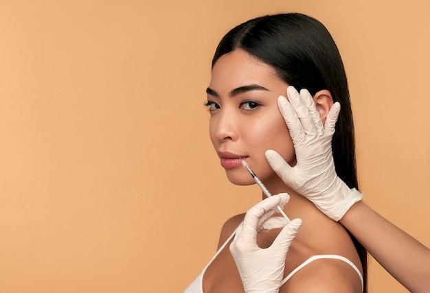 Молодая азиатская женщина с чистой сияющей кожей получает инъекции ботокса для подтяжки контура, увеличения губ на бежевом