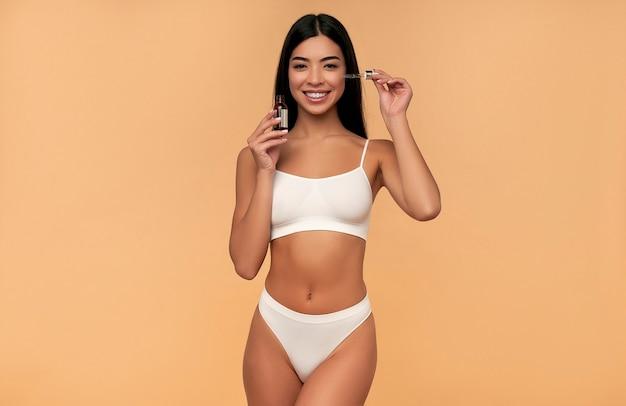 Молодая азиатская женщина с чистой сияющей кожей в белом нижнем белье использует увлажняющую сыворотку на бежевой стене.