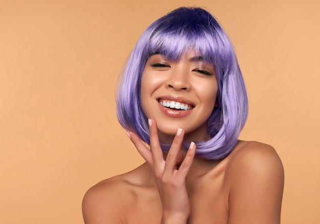 Young asian woman with clean radiant skin in a purple wig and bright hair on beige