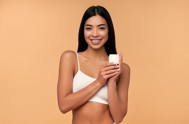Молодая азиатка с чистой сияющей кожей наносит увлажняющий крем для лица на бежевую стену.