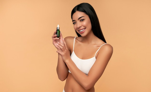 Young asian woman with clean radiant skin in white lingerie holds a moisturizing serum on beige