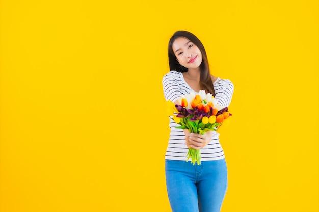 カラフルな花を持つ若いアジア女性
