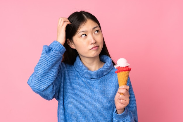 Young asian woman with a cornet ice cream isolated having doubts