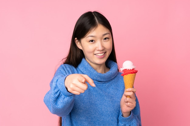 Young asian woman with a cornet ice cream isolated on pink wall points finger at you with a confident expression