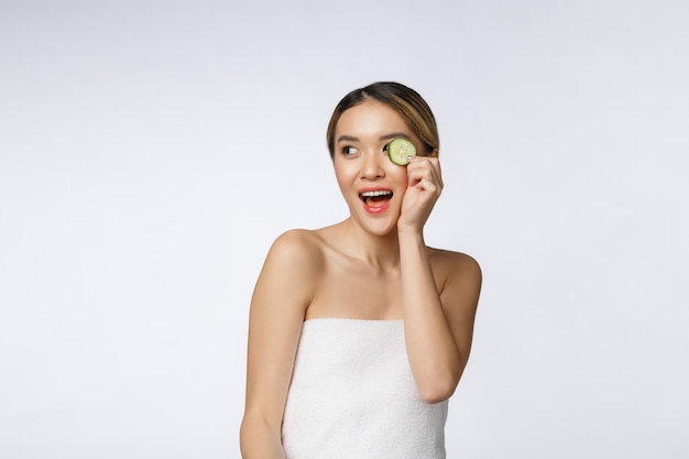 Young asian woman with cucumber slice in her hands isolated on white background.