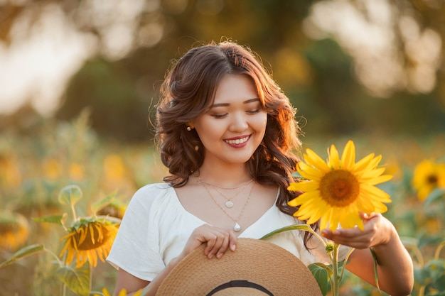 日没時のひまわり畑で巻き毛の若いアジアの女性。太陽の下で若い美しいアジアの女性の肖像画。夏。