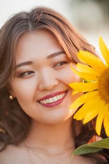 일몰 해바라기의 분야에 곱슬 머리를 가진 젊은 아시아 여자. 햇볕에 젊은 아름 다운 아시아 여자의 초상화. 여름.