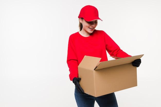 Молодая азиатская женщина с работником службы доставки в униформе